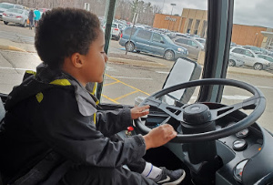 Little boy sitting in the driver seat of the bus