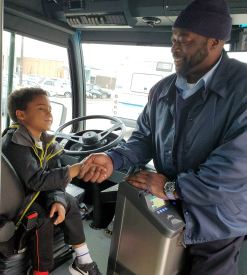 Little boy shakes hand of bus driver