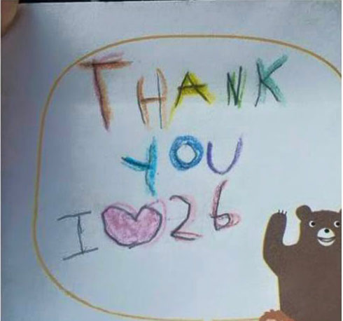 "Child's crayon drawing that reads: ""Thank you. I heart 26."""
