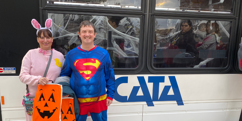 A man dressed as superman stands next to a woman dressed as a bunny in front of a CATA bus