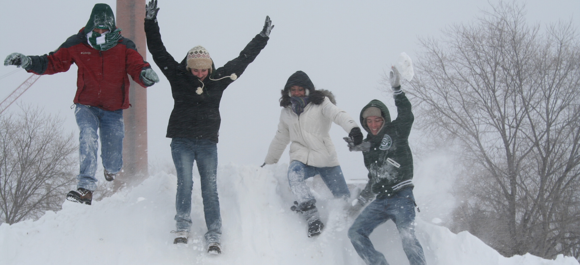 4 kids in MSU apparel jumping on a snow bank