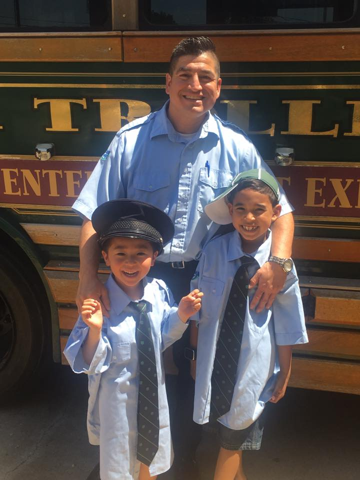 Bus driver with two little boys in CATA uniforms