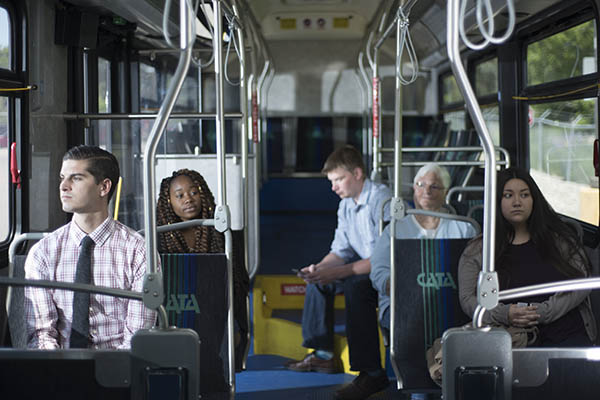 People sitting on CATA bus following safety rules